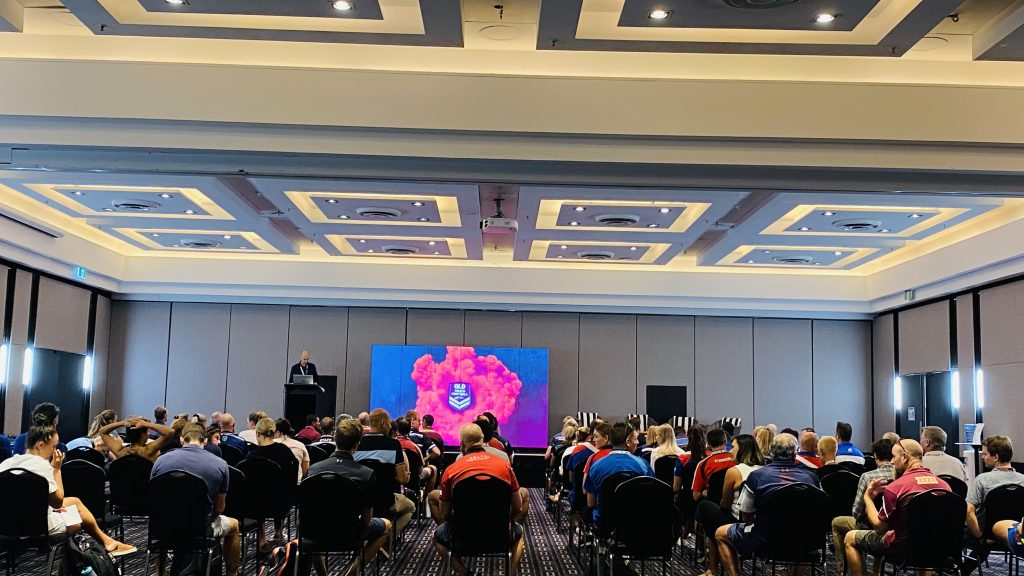An image of ECKOO LED Media panels being used for a conference presentation. Rows of attendees look on at the presenter. The screen shows the Queensland Touch Football logo, surrounded by an explosion of pink on a blue background.
