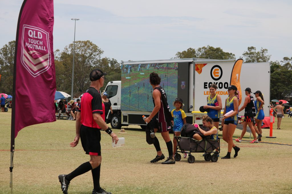An image of a group of players walking past the ECKOO LED Media Truck. There is a maroon QLD Touch flag in the foreground, and a referee walking in the opposite direction. He wears a pink polo shirt.