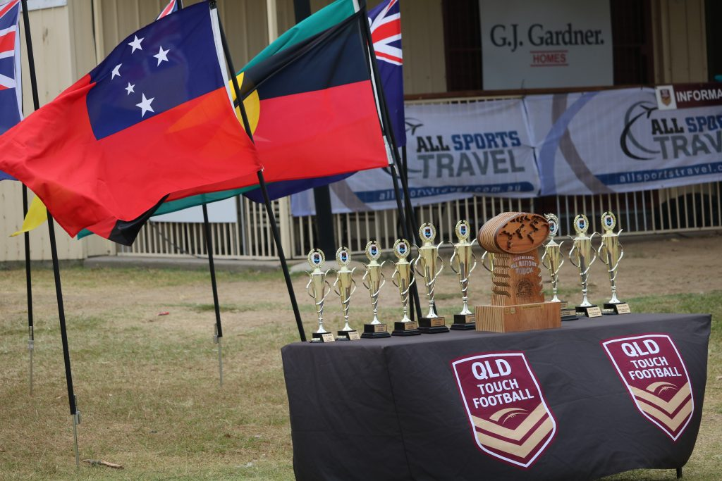 An image of Queensland Touch Football trophies lined up on a table. The Australian, Aboriginal and Samoan flags are visible in the background.